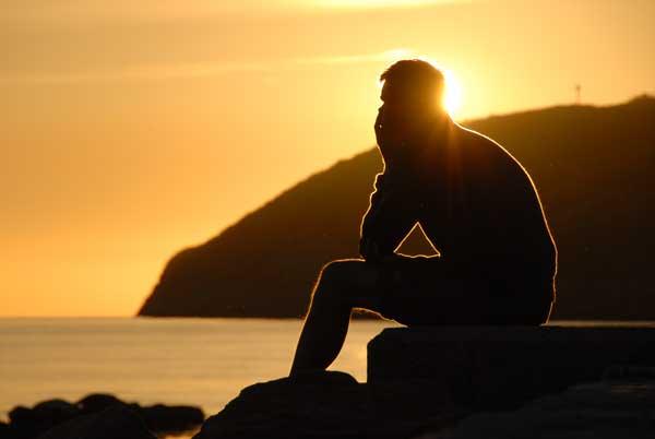 Penseur devant soleil couchant